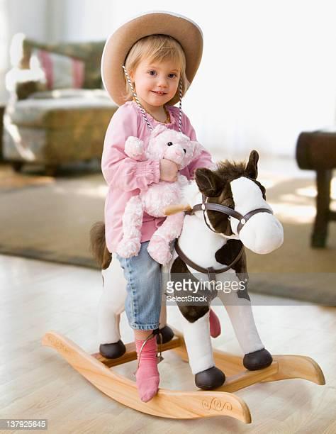 Fille sur un cheval à bascule