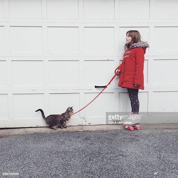 Girl on Roller Skates Walking Cat