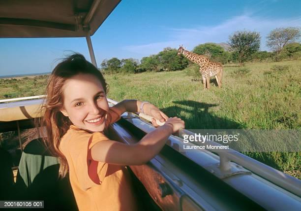 Girl (10-12) on safari bus, giraffe in background, portrait
