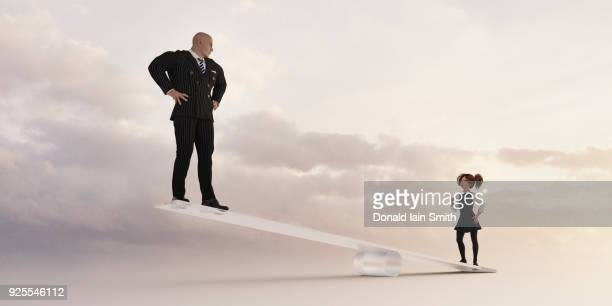 girl on seesaw lifting businessman - inequality stock photos and pictures