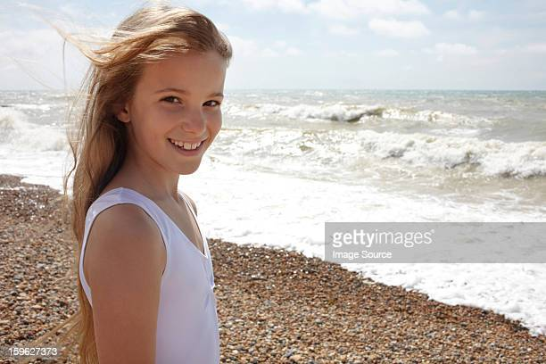 girl on shingle beach by the sea, smiling at camera - saltdean stock pictures, royalty-free photos & images