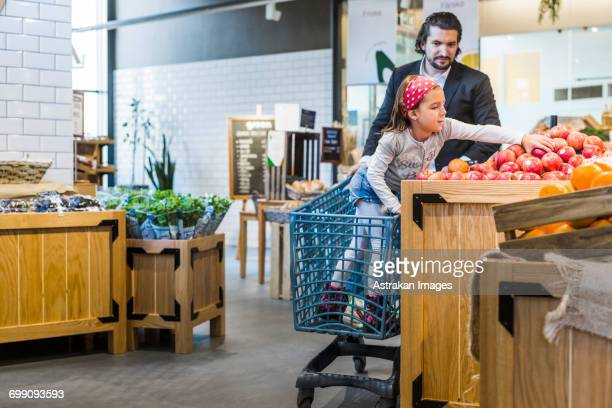 girl on shopping cart buying apples with father in supermarket - girl mound stock pictures, royalty-free photos & images