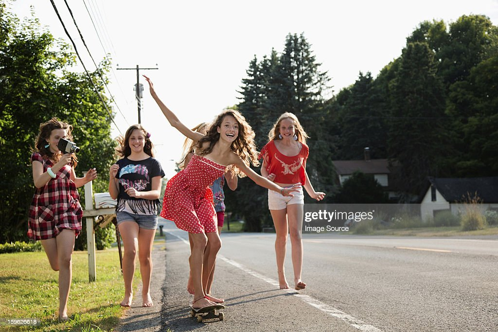 Girl on skateboard with friends : Stock Photo