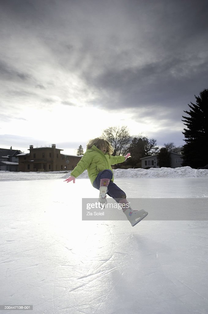 Girl (4-6) on skates falling on frozen lake, winter : Stock Photo