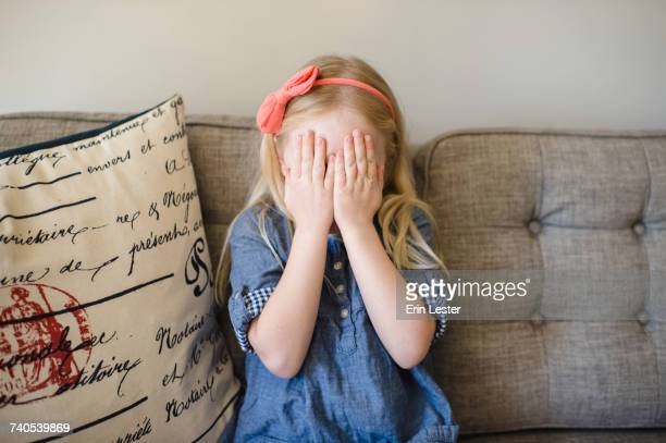 Girl on sofa covering her face with hands