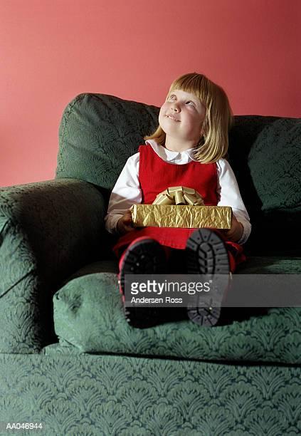 Girl (5-7) on sofa holding gift