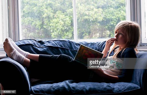 girl on sofa reading book - little girls socks stock photos and pictures