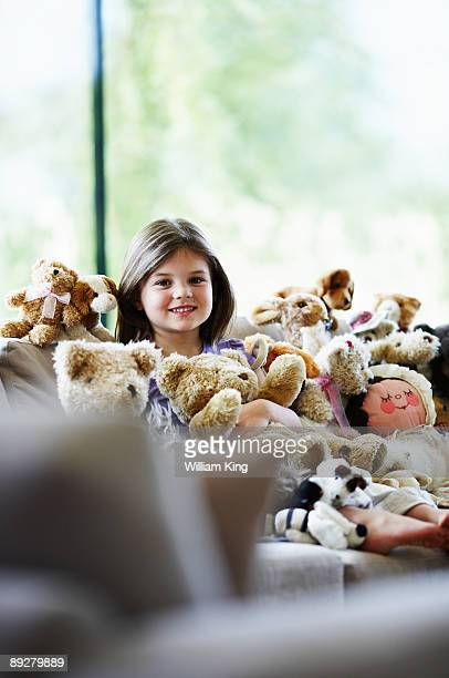 girl on sofa with soft toys - girl mound stock pictures, royalty-free photos & images