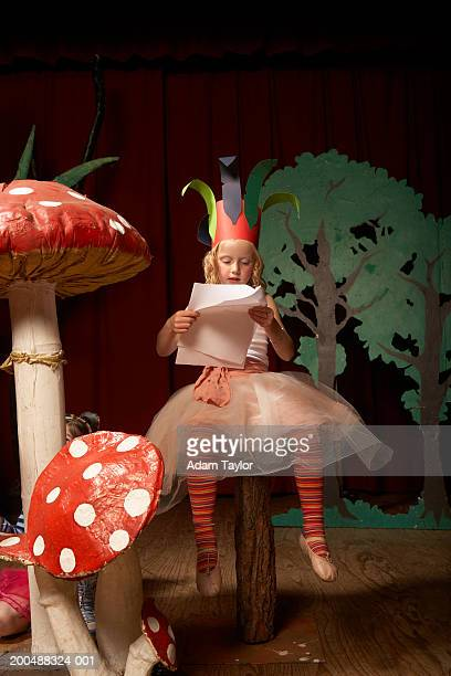Girl (4-6) on stage, sitting on giant toadstool practicing lines