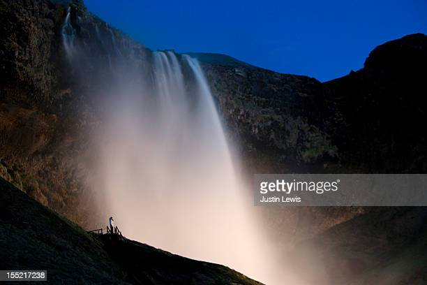 Girl on stairs by huge waterfall at night