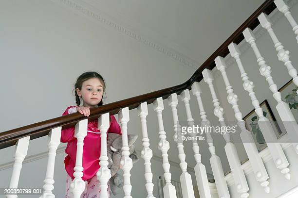 Girl (5-7) on stairs, looking over bannisters, low angle view