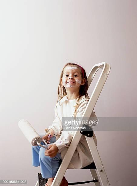 Girl (4-6) on step ladder holding paint roller, portrait