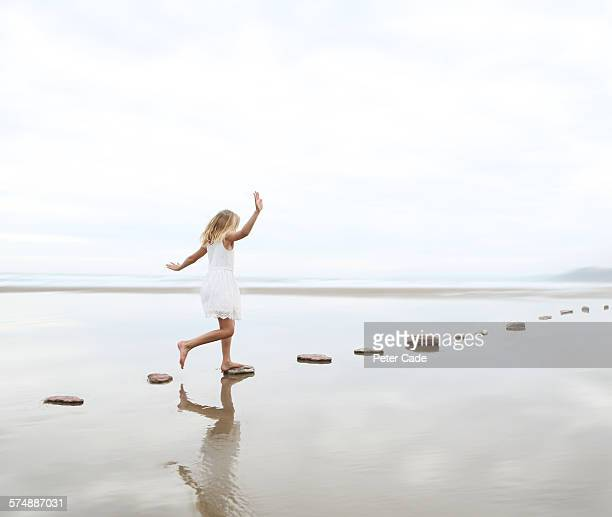 girl on stepping stones on beach - barefoot stock pictures, royalty-free photos & images