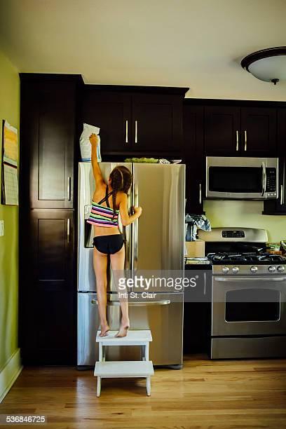 Girl on stool reaching for something on fridge