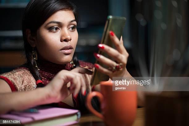 Girl on study table with books coffee mug using smartphone.