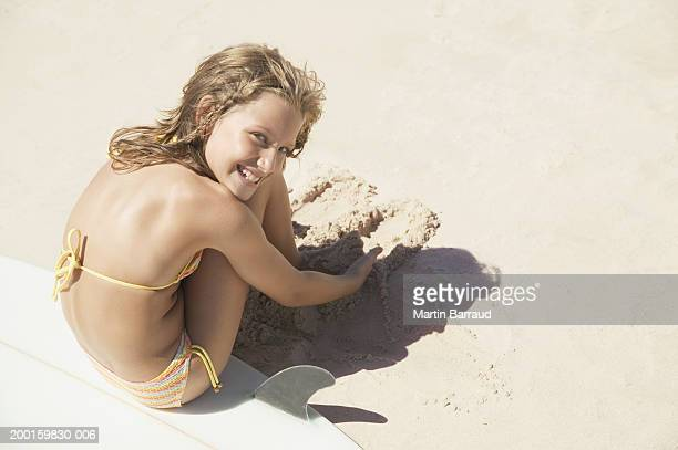 Girl (8-10) on surfboard, digging in sand, portrait, elevated view