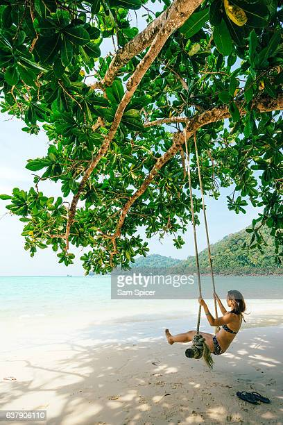 Girl on swing in tropical island beach paradise, Thailand