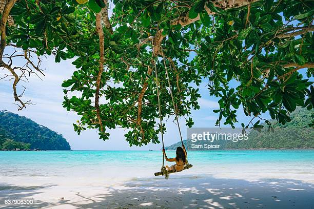 Girl on swing in tropical island beach paradise, Thailand
