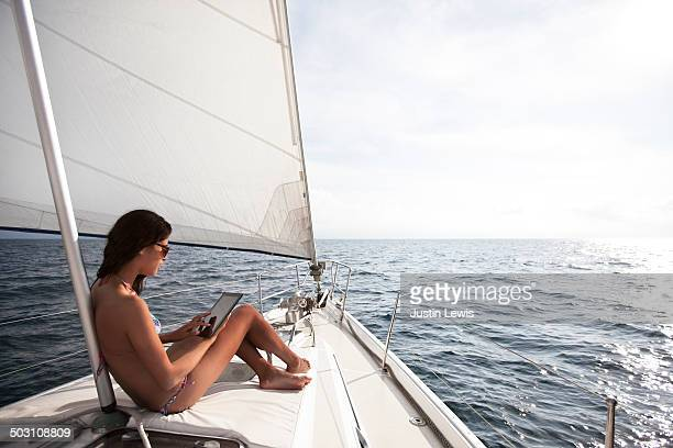 Girl on ipad while sunbathing on front of sailboat