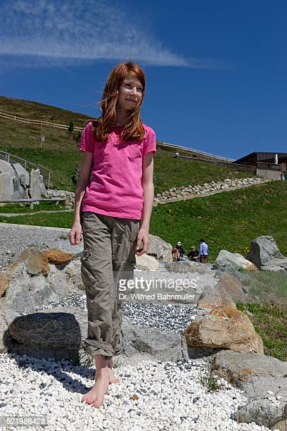 Girl on the barefoot path on the Watles Adventure Mountain, near Mals, Vinschgau, Province of South Tyrol, Italy