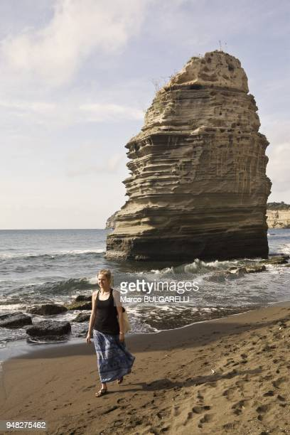 Girl on the beach at the faraglioni of Procida on June 11 2012 in Procida Italy