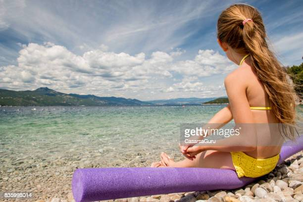 Girl On The Beach Sitting On Foam Noodle And Looking At The View