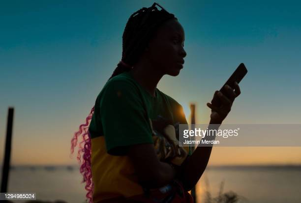 girl on the beach using phone - africa stock pictures, royalty-free photos & images