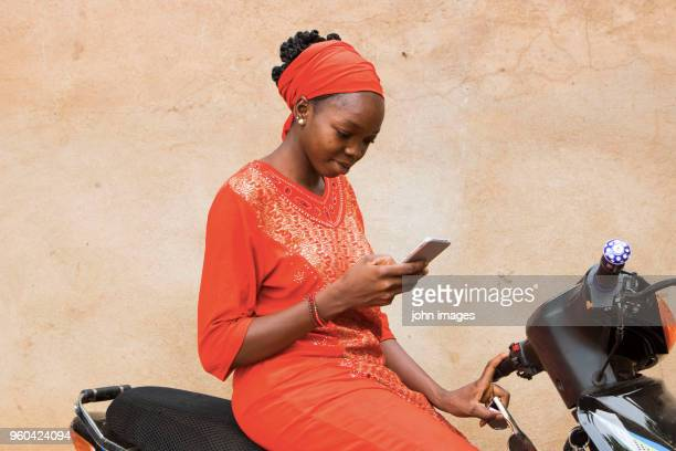 a girl on the bike looking at her phone - mali photos et images de collection