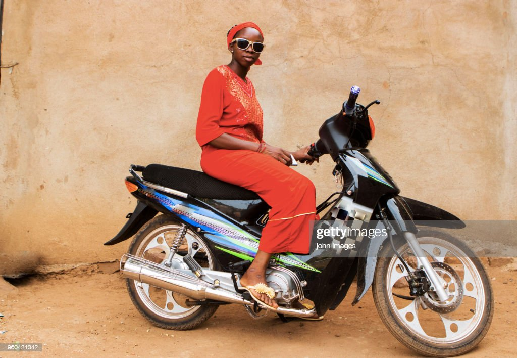 A girl in a telephone communication on the motorcycle informing her friend about having a means of transport which is the Djakarta motorbike that many people buy here in Mali