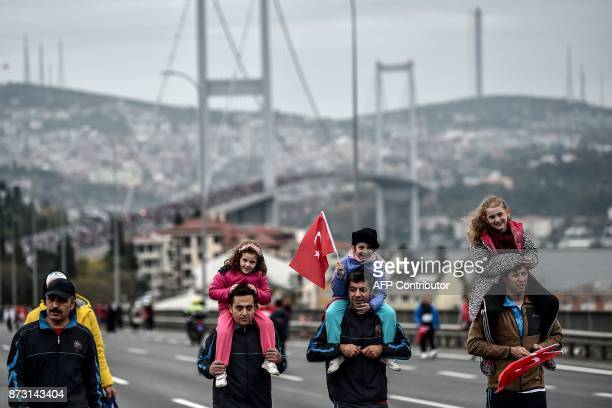 A girl on the shoulders of a man waves a Turkish national flag as they walk with other people after crossing the July 15 Martyrs' Bridge known as the...