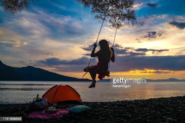 girl on the swing at sunset. - paesaggio marino foto e immagini stock