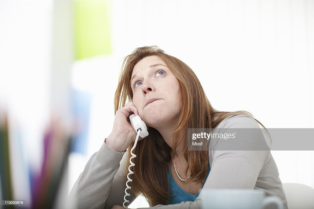 Girl on the telephone sitting at desk : Foto de stock