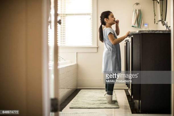 Girl on tiptoes brushing teeth in bathroom