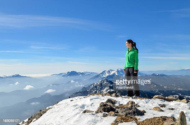 Girl on top of a snowy mountain. Winter landscape