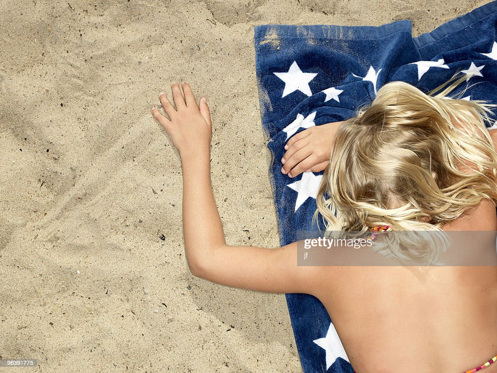 Girl on towel at the beach : Stock Photo