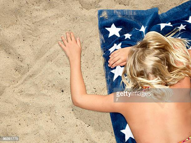 girl on towel at the beach - girls sunbathing stock pictures, royalty-free photos & images