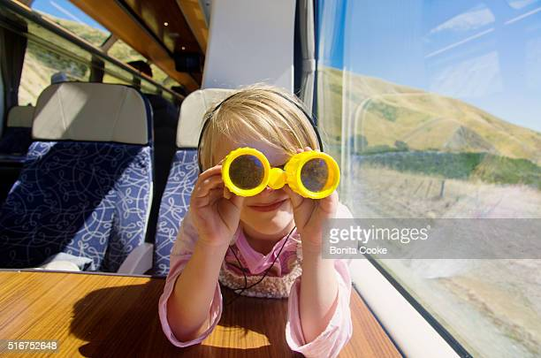 Girl on train, playing with toy binoculars