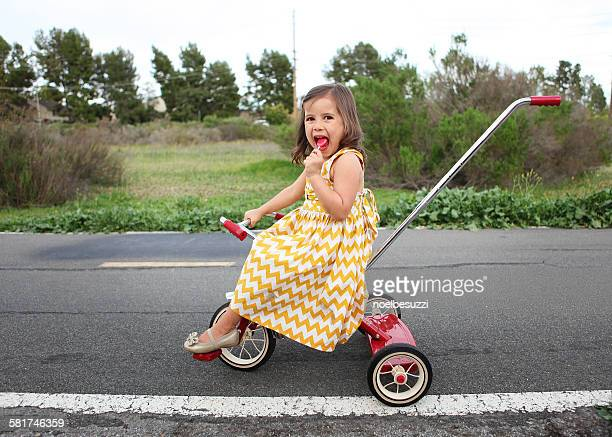 Girl on tricycle eating lollipop