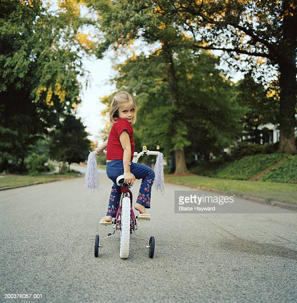 Girl (3-5) on tricycle looking over shoulder, portrait