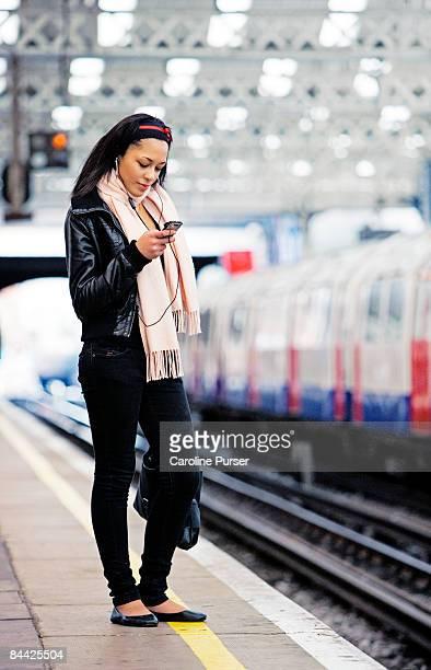 girl on tube platform waiting for train - vertical red tube fotografías e imágenes de stock