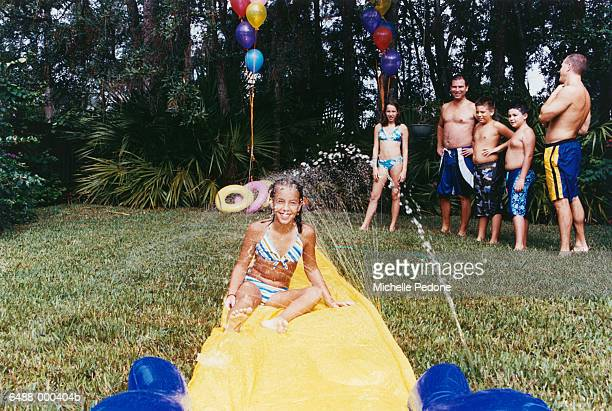 Girl on Water Slide in Garden