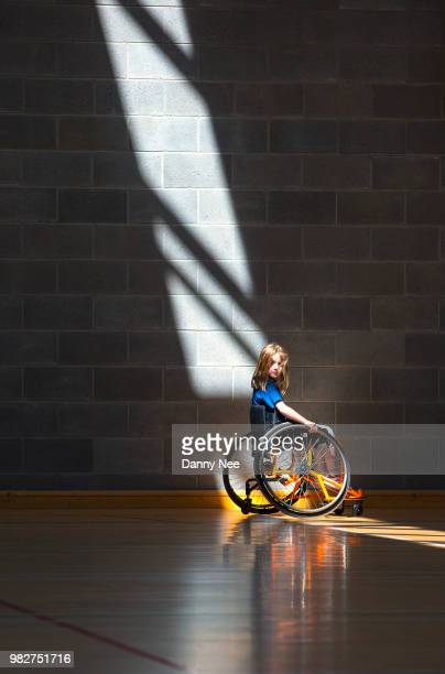 Girl (8-9) on wheelchair in gym