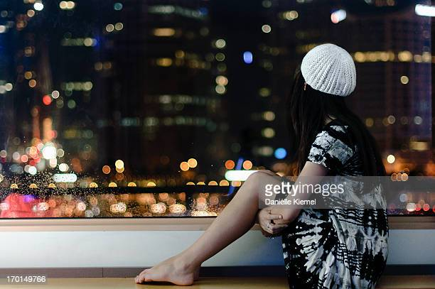 girl on windowsill looking out at the city lights - darling harbour stock pictures, royalty-free photos & images