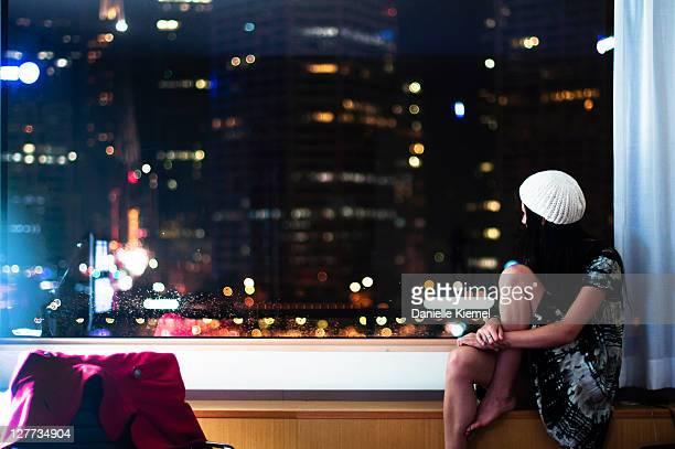 Girl on windowsill watching city below