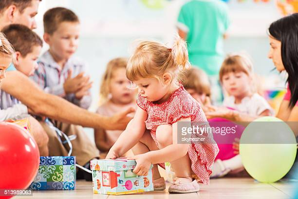 girl opening birthday present. - birthday gift stock pictures, royalty-free photos & images