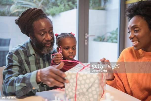 Jeune fille ouverture cadeau anniversaire avec grand-père et ma mère regarder