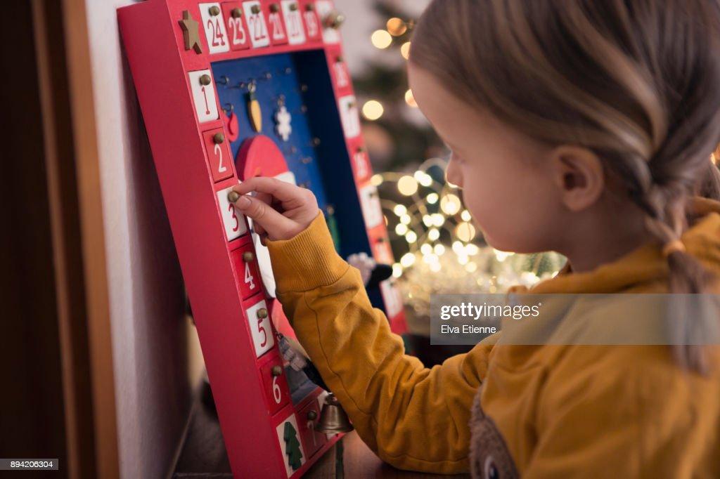 Girl (4-5) opening Christmas advent calendar : Stock Photo