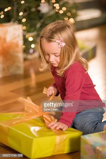 Girl (3-5) opening Christmas gift