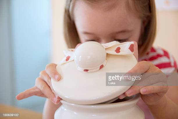 Girl opening cookie jar in kitchen