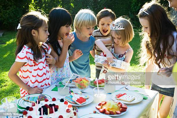 girl opening gift at birthday party as friends watch - birthday gift stock pictures, royalty-free photos & images